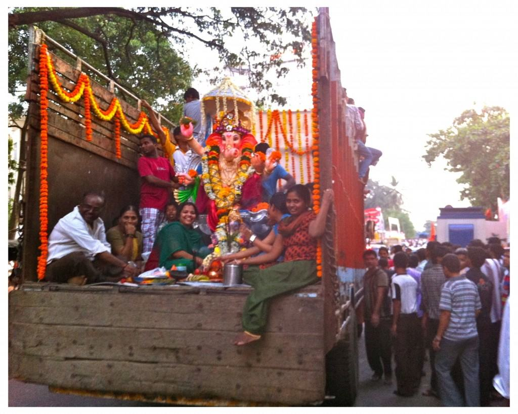 A procession truck slowly making its way through throngs of devotees